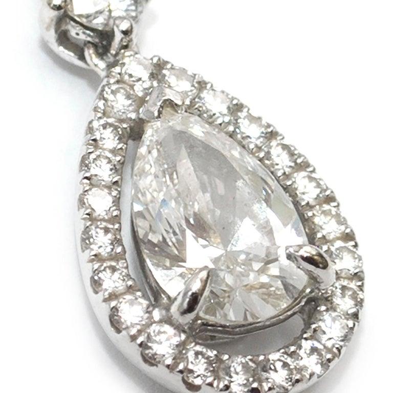 Bespoke diamond encrusted white-gold pendant   - White gold pendant  - White diamond-pave encrusted loop - Round cut white diamond drop - Pear cut white diamond pendant, diamond pave encrusted  This pieces features:  - 1x 0.7 ct pear cut diamond