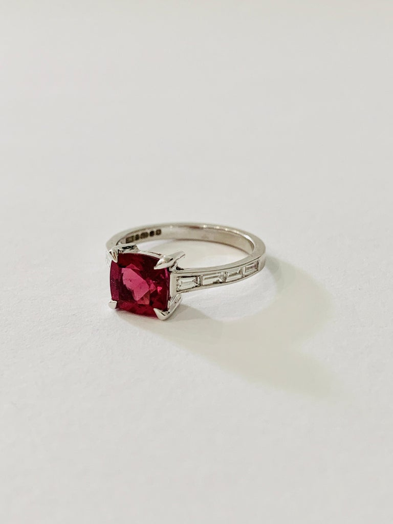 This Bespoke ring is set with a Premium Grade Rubellite*  and the design has baguette diamonds in the band.   A CAD was created to make sure this stone was shown off to its best.   This design lends itself to either being a unique engagement ring or