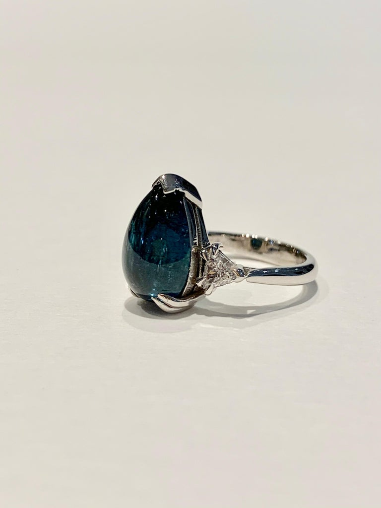 This amazing blue Tourmaline* pear cut cabochon* is eye clean and set in a double claw design in 18ct White Gold.  A BESPOKE design using a CAD  to ensure this stone was presented as its best.  The ring also has 2 x .20 Trillion Cut diamonds as