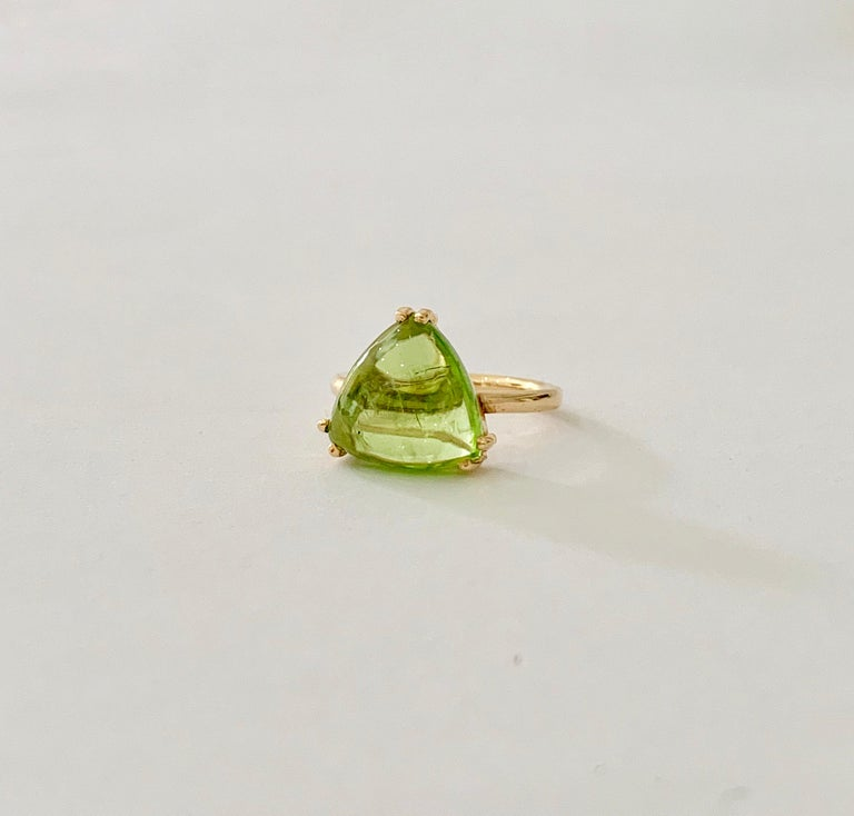 This Bespoke Peridot* ring was designed using a CAD especially to compliment the cabochon* trillion cut stone and, therefore,  making it totally unique.  The Peridot is a luxurious light green with a jelly effect from the cabochon cut.  The stone