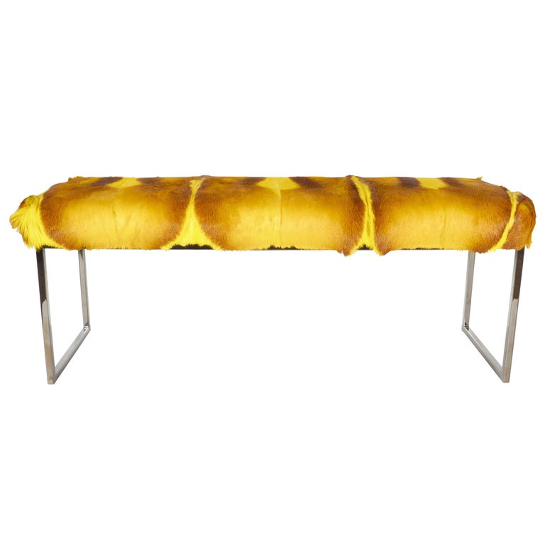 Mid-Century Modern style bench upholstered in stunning African springbok hide. Comprised of several hides featuring four spine details. Hand-dyed in vibrant yellow with varying hues of gold and deep brown. Streamline base in a black nickel finish.