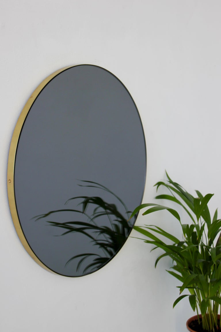 Charming bronze tinted round mirror with an elegant brass frame, with a polished or brushed option. Designed and hand-crafted in London, UK. The detailing and finish, including visible brass screws, emphasize the crafty and quality feel of the