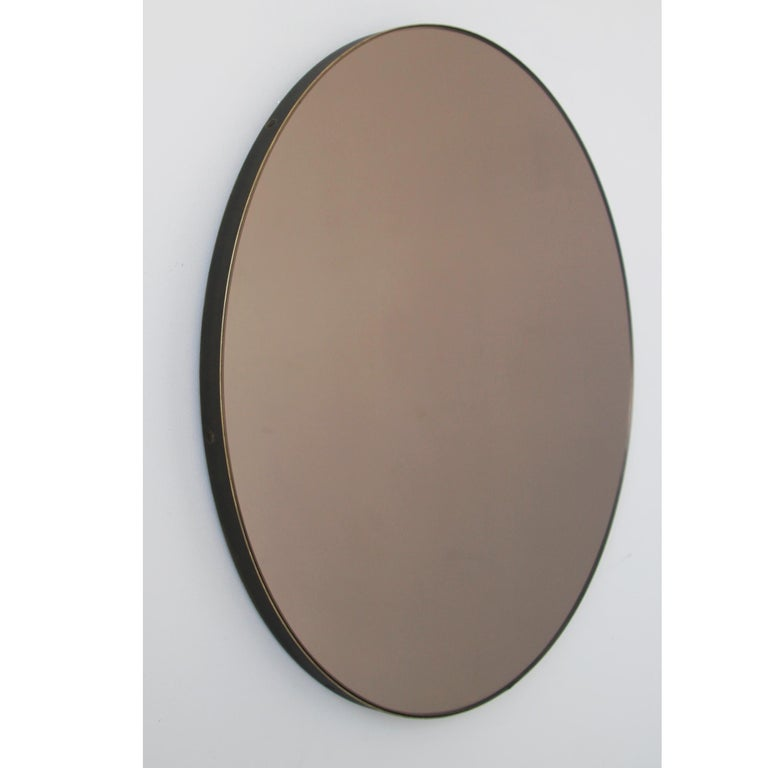 Smart vintage style bronze tinted round mirror with a bronze patina brass frame. Designed and handcrafted in London UK. The detailing and finish, including visible brass screws, emphasize the craft and quality feel of the mirror, a true signature of