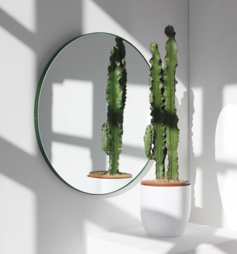 Delightful handcrafted silver round mirror with a funky green frame.