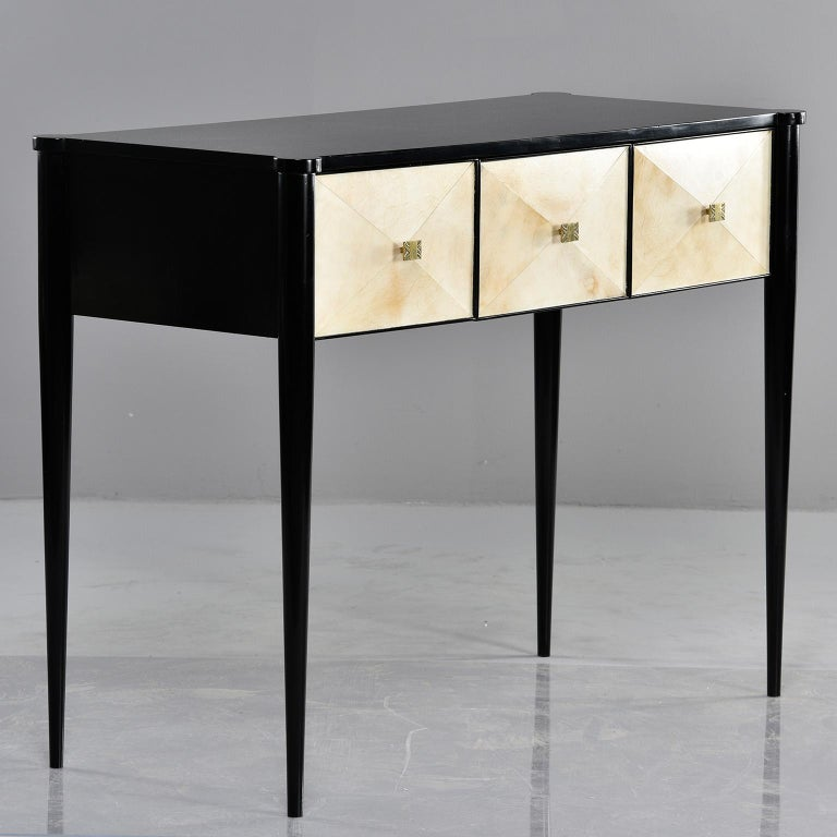 Custom created by English cabinet maker, this console has an ebonized wood frame with tapered legs and three functional drawers with vellum covered fronts. Brass hardware.
