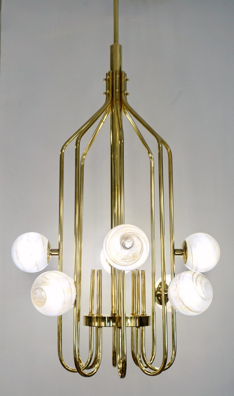 A contemporary innovative custom modern chandelier, entirely handcrafted in Italy. The handmade geometric cylinder brass structure, resembling a sleek birdcage, has a very organic curvilinear shape decorated with 8 round globes in an innovative
