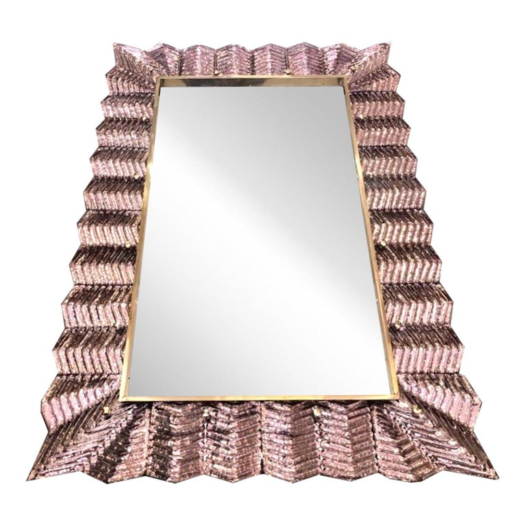 Venetian contemporary Couture design rectangular wall mirror, custom made in Italy, framed with a thick border in high quality blown Murano art glass in blush rose color, artistically decorated with a typical Art Deco reeded sculpture pattern that