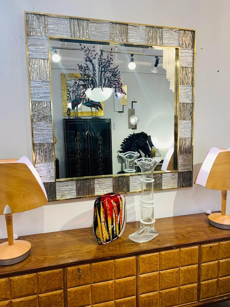 A contemporary geometric mirror with a sophisticated style, entirely handcrafted in Italy, a sculpture piece with exceptional craftsmanship and innovative production, customizable in sizes, finishes, and glass colors: the decorative frame, inset in