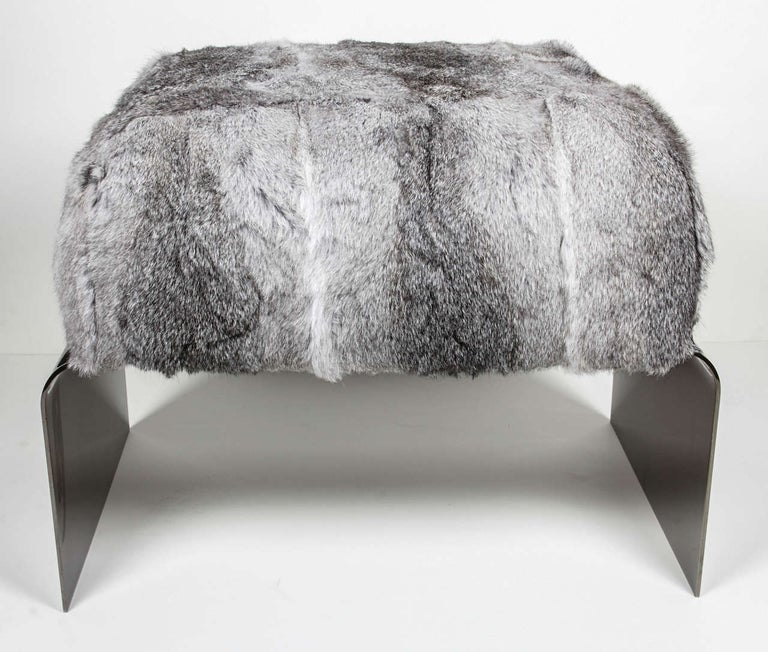 Exquisite Mid-Century Modern style stool with waterfall base design in polished black nickel. Upholstered in luxurious rabbit fur in variant hues of grey. Great accent piece for any room and great as an ottoman.