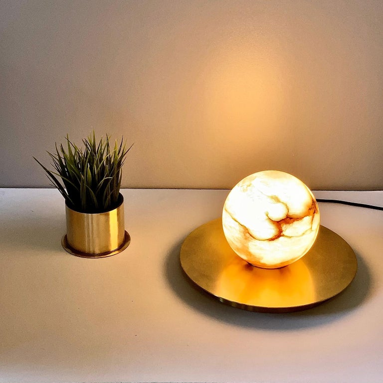 Cosulich Interiors in collaboration with Matlight Studio, this organic table lamp, part of the Alabaster Moon Collection, entirely handmade in Italy, emphasizes the properties of alabaster as a diffuser, with its warm color and texture of its amber