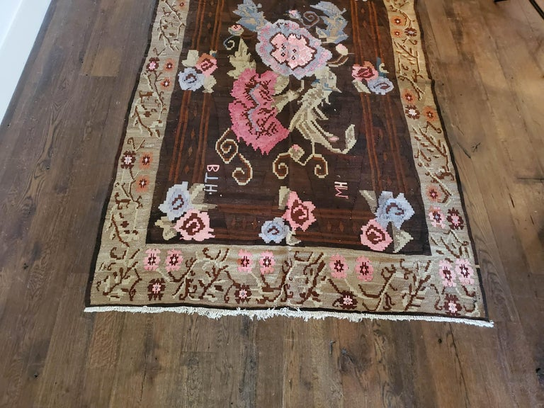 Floral bessarabian design. A hardy strong flat-weave with elaborate pink flowers floating and smaller blossoms in pale blue, ivory, and brown.