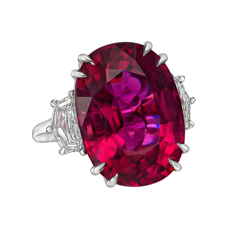 Cocktail ring, centering an oval-shaped pink tourmaline weighing 20.45 carats flanked by trapezoid-cut diamonds, mounted in polished platinum.  Two diamonds weighing 1.37 total carats (F-G color, VS1-VS2 clarity)