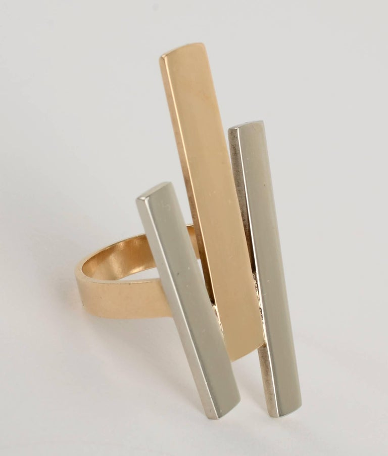 Striking geometric ring by modernist designer, Betty Cooke. Cooke placed one gold rectangle between two of sterling. Each is a different size. The gold rectangle measures 1 3/16