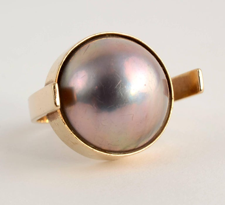 Mabe pearl and gold asymmetrical ring by modernist designer, Betty Cooke. The ring has a gray mabe pearl with mauve undertones that measures 17.3 mm in diameter. The pearl is set off center with an open,  adjustable shank. The ring is size 7 but can