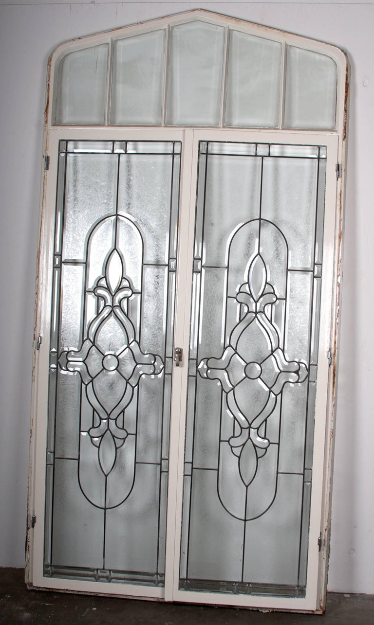 This is a set of 12 arched metal window frames, with wonderful beveled, partially