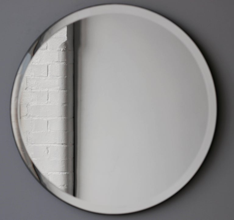 Delightful crafted silver grey mirror frameless with an elegant bevel and velvet backing.  Measures: Diameter 80cm / 31.5