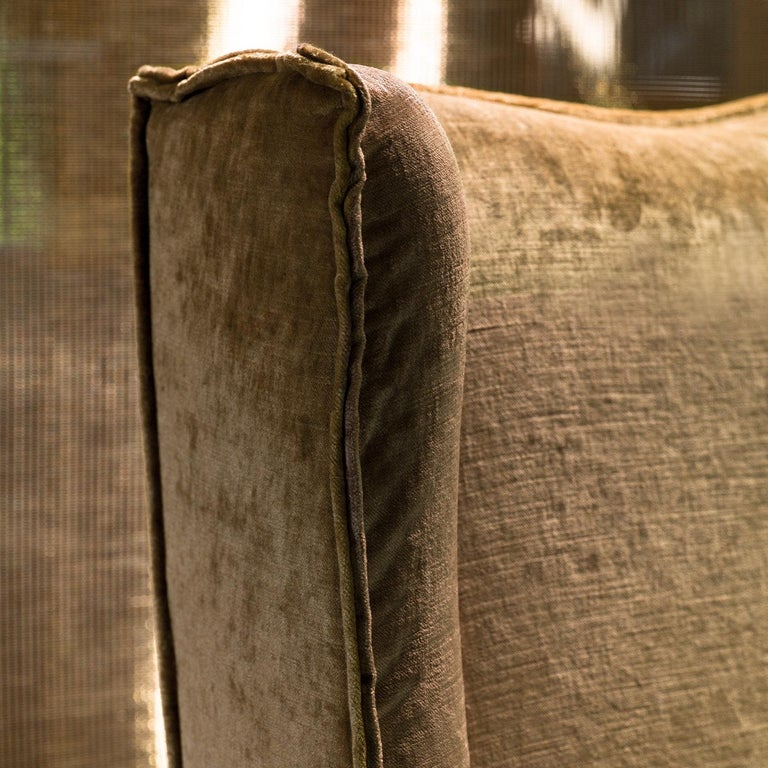 Exuding elegance through its delicately curved profile, this refined armchair features a protective lining for the generous polyurethane padding underneath. The wooden structure, marked by concave profiles, is wholly dressed in soft beige velvet