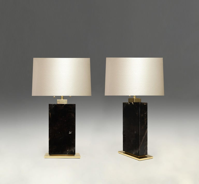 A pair of block form smoky rock crystal lamps with polished brass bases. Created by Phoenix Gallery, NYC. To the rock crystal: 12.5