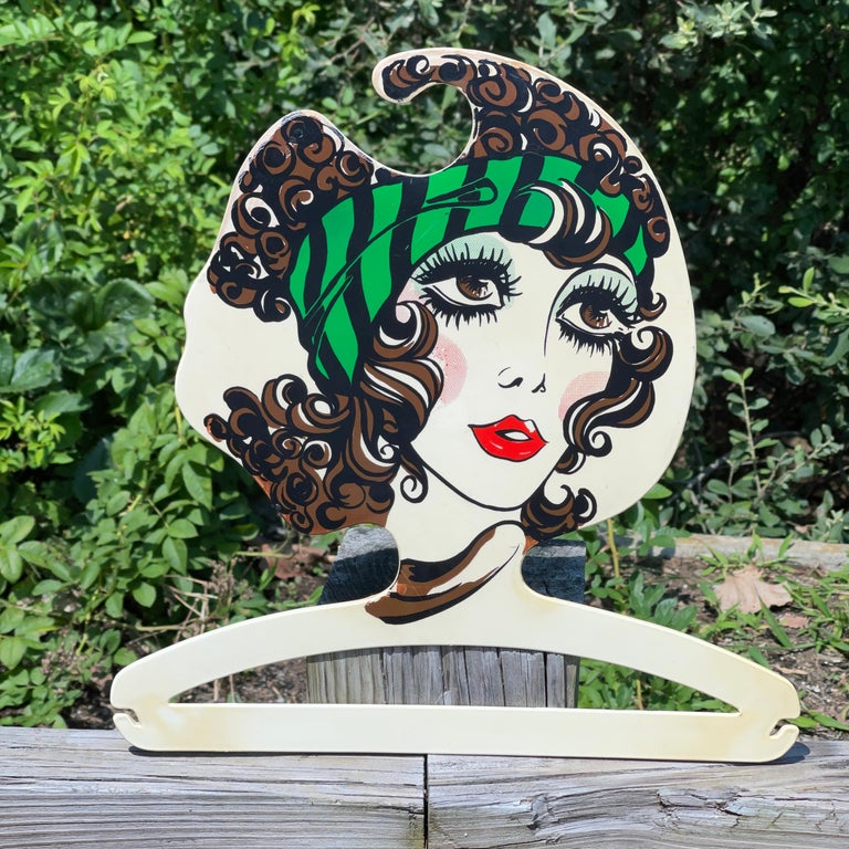 1960's Italian plastic coat hanger with stylized head and face of a fashionable young woman applied via lithograph transfer. Produced in Italy by BG Milano (No relation but I love the sound of it!) Alas, we have just this one but continue to hunt