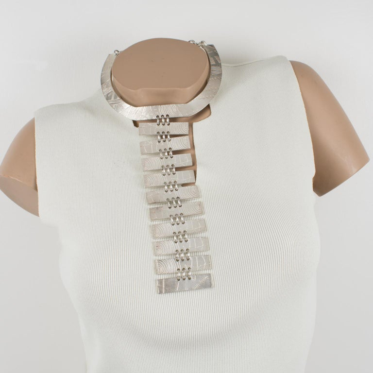 Impressive futuristic silver plate plastron necklace by Nelly Biche de Bere, Paris. Chunky massive oversized neck-tie shape with a graffiti design. The intricate design features stylized lines and curves like hieroglyph inscriptions. Hook closing