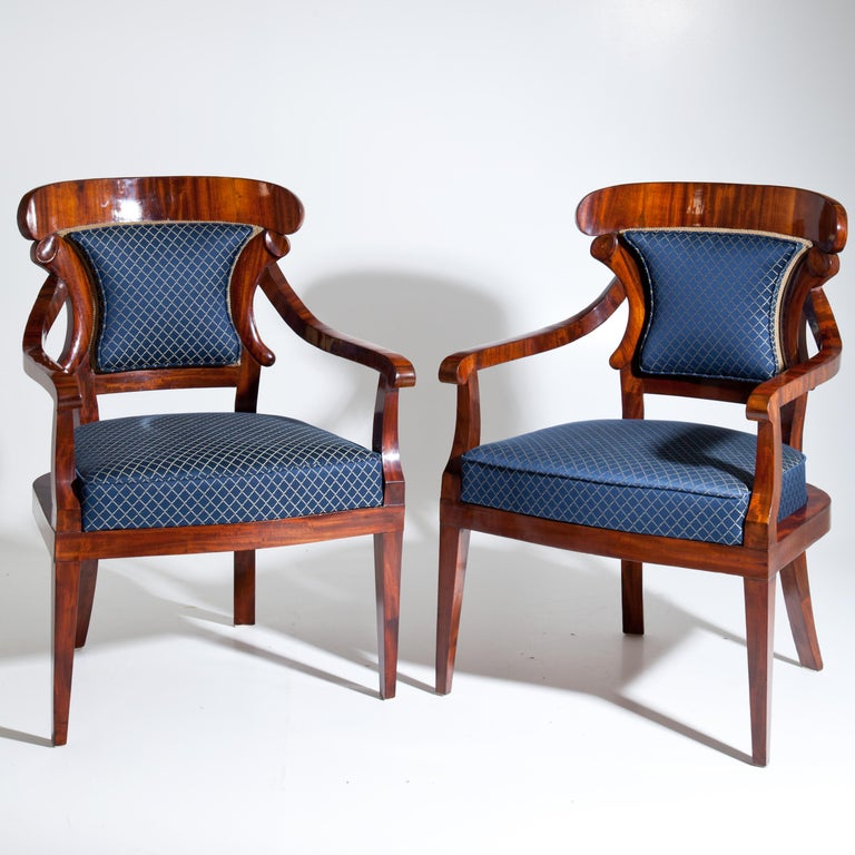 Pair of Biedermeier mahogany armchairs with curved armrests and shovel-shaped backrests. The vertical struts of the backrests are modelled on stylised cornucopias. The seats and backrests are newly covered with a blue satin fabric with a gold