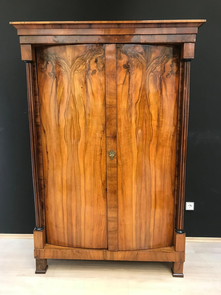 Very classic, early Biedermeier Armoire with convex/cylindrical doors and beautiful fluted and ebonized full-columns.  The armoire's front and side are veneered with a amazingly beautiful book-matched walnut.  Inside the doors are veneered in maple.