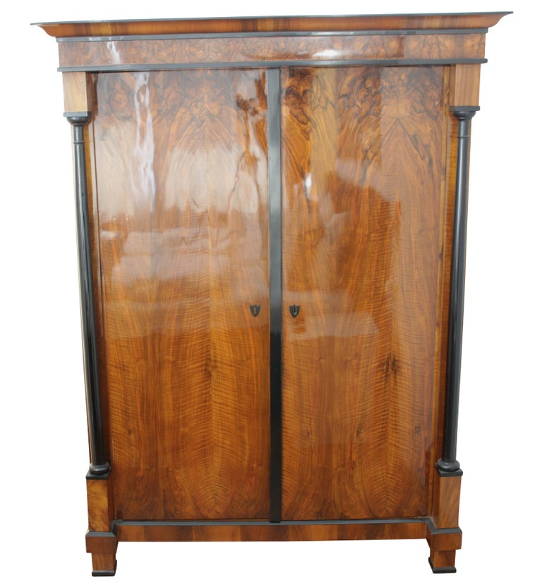 Splendid early Biedermeier armoire from Austria, circa 1820.   The two-door closet has two ebonized full columns and a beautiful book-matched walnut veneer. Underneath the cornice, there is a skirting made of  lovely walnut roots veneer.  The