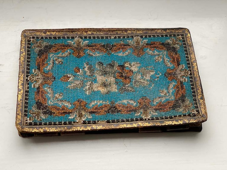 Elaborate Biedermeier notebook with pearl application on front and back. The book is from Germany from mid-late 19th century. It is leather covered and the beaded application has golden floral ornaments.