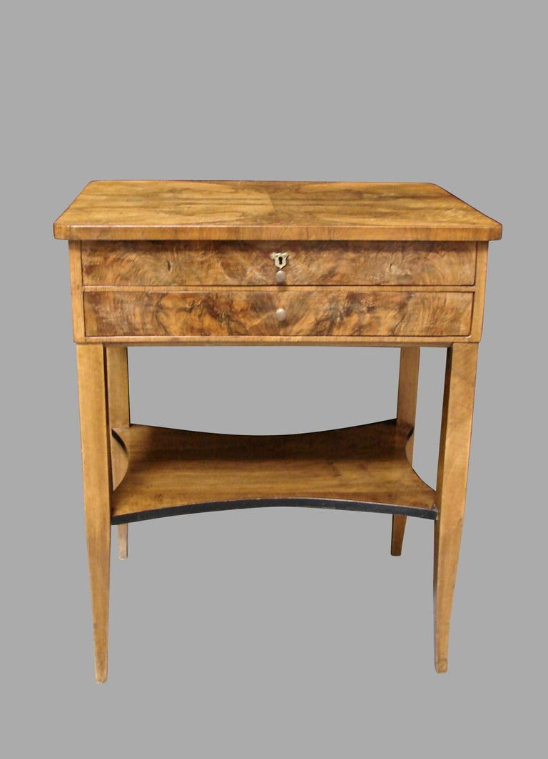 A nice quality Austrian or German Biedermeier work table, the book matched well-figured top over 2 drawers, one fully fitted, above a lower shelf with an ebonized edge, supported on square tapered legs. Circa 1840