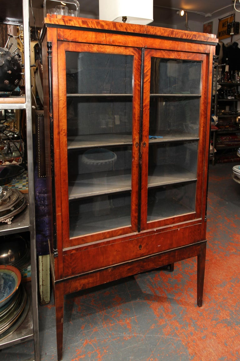 Biedermeier cabinet on lovely tall tapered legs. Old glass in double doors, lock on left side door to keep it from swinging open, and key to lock the cabinet. Interior shelves still lined with blue, as found. Very usable cabinet and a great size.