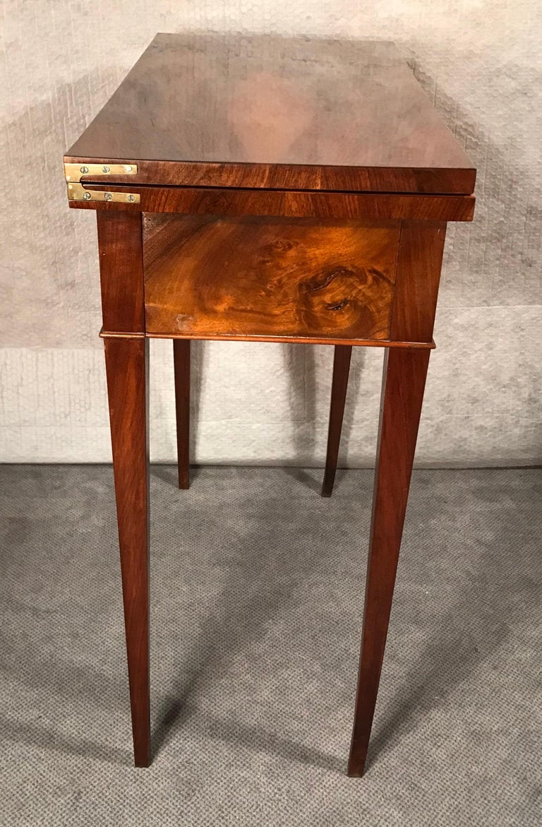 Biedermeier card or console table, South German 1820. The table has beautiful walnut veneer on top, sides and legs. The top can be folded out and rests on the pulled out apron and rear legs of the table. The folded out top is covered with green