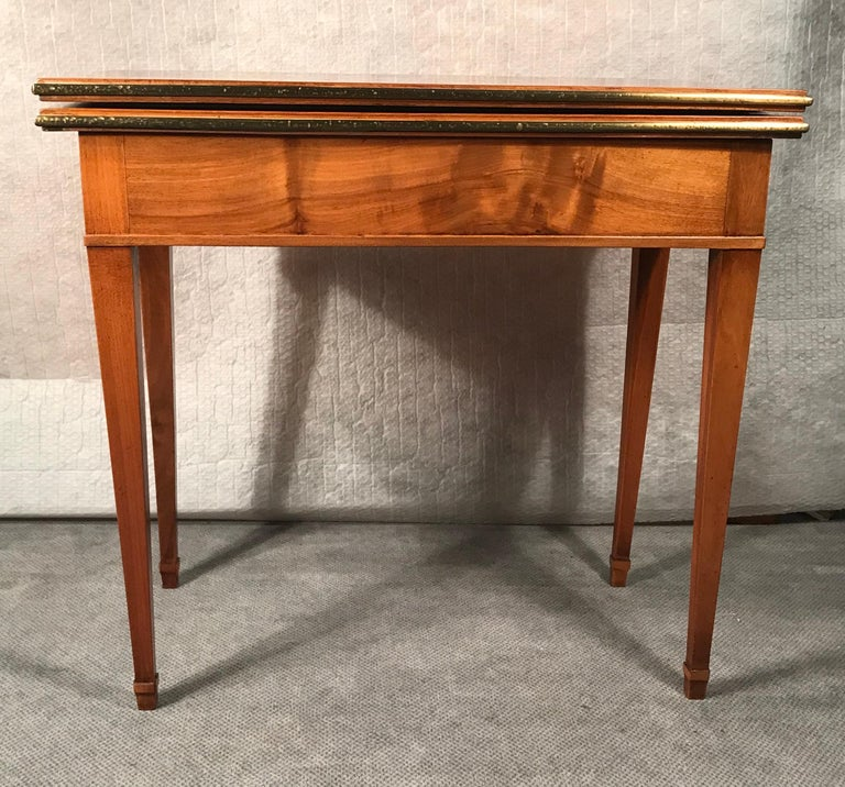 Biedermeier card or console table, South German 1820. The table has beautiful walnut veneer on top, sides and legs. The top can be folded out and turned and then rests on the base of the table. The folded out top is covered with yellow velvet.  The