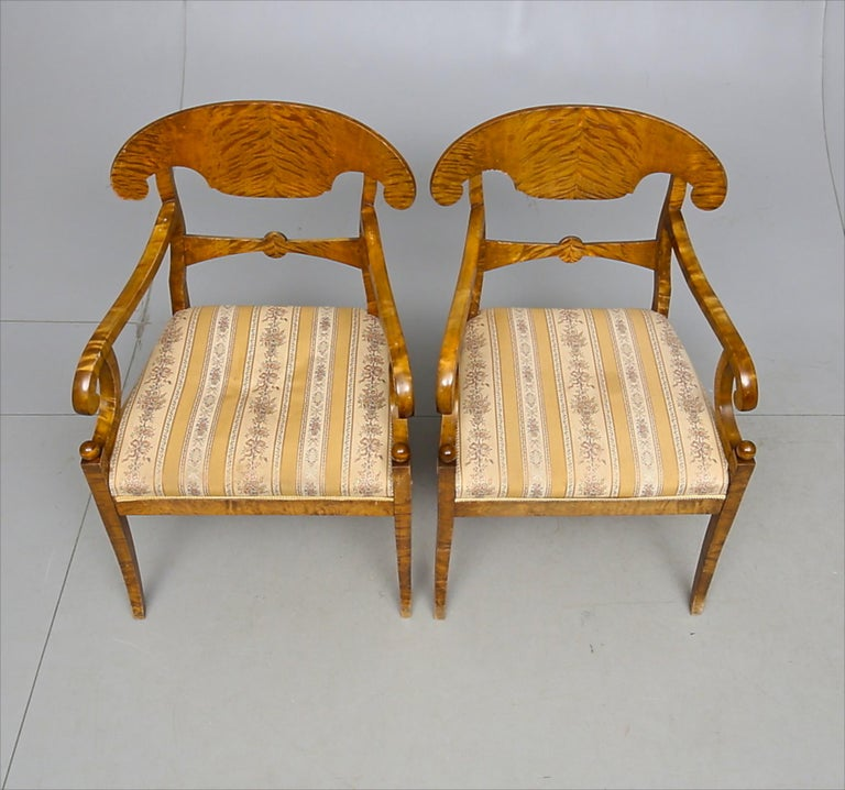 Swedish Biedermeier Empire pair of carver chairs in highly quilted golden birch veneers finished in the Classic honey color French polish finish with ormolu roundel on the arms.  They have fully webbed seats for maximum comfort and the gently