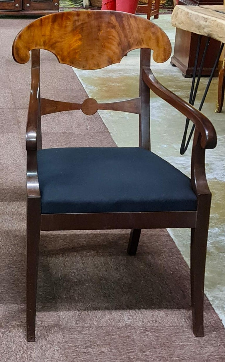 Swedish Biedermeier Empire pair of carver chairs in highly quilted mahogany veneers finished in the Classic darker color French polish finish with ormolu roundel on the arms.  They have fully webbed seats for maximum comfort and the gently curved