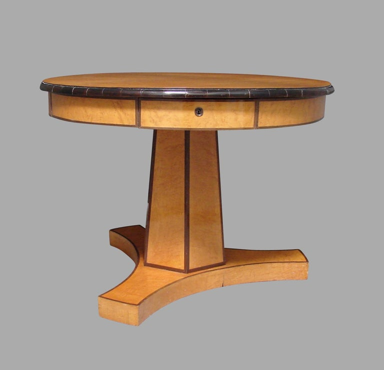 A good quality Austrian Biedermeier satin birch or maple center table, the top with an ebonized edge above 4 functional drawers resting on a hexagonal column ending in a tripod base resting on later casters. This is a stylish and elegant piece of
