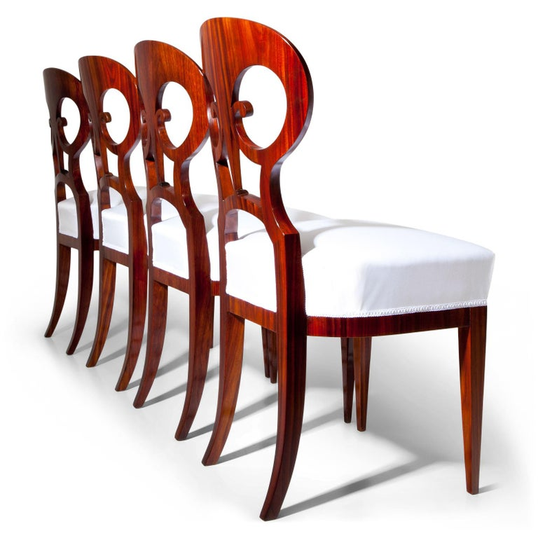 Set of six Biedermeier chairs out of mahogany, standing on tapered legs. The pretzel-shaped backrests show ebonized thread inlays. The seats were reupholstered with a white fabric.