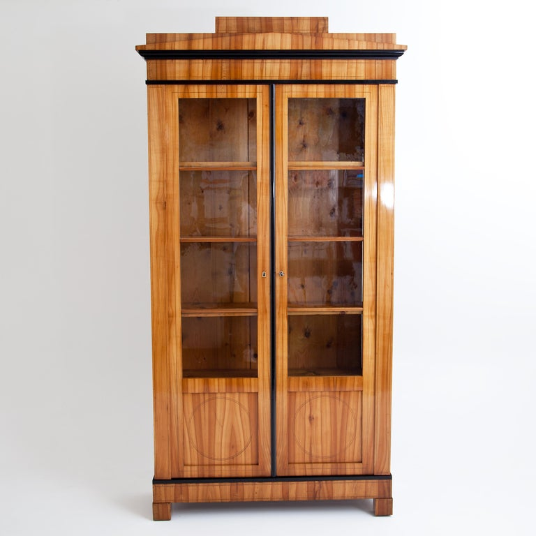 Two-door bookcase on low square feet with doors in 4/5 glazing and stepped cornice. The plinth and cornice are optically structured by ebonized profiles and harmoniously united by the vertical ebonized strip. The corpus is veneered in cherrywood and