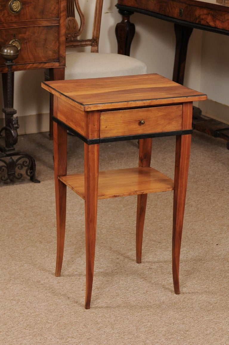 A Biedermeier side table in cherrywood with drawer, ebonized detail and lower shelf ending in tapered splayed legs.