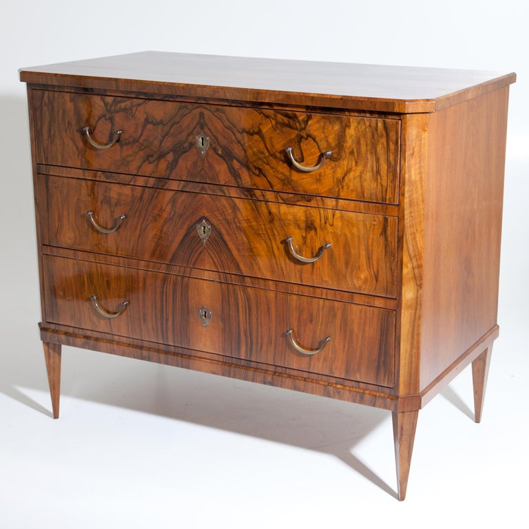 Chest of drawers standing on square pointed feet with three drawers and bevelled corners. The beautiful walnut veneer is mirrored on the front. Expertly restored condition. Fittings are recent.