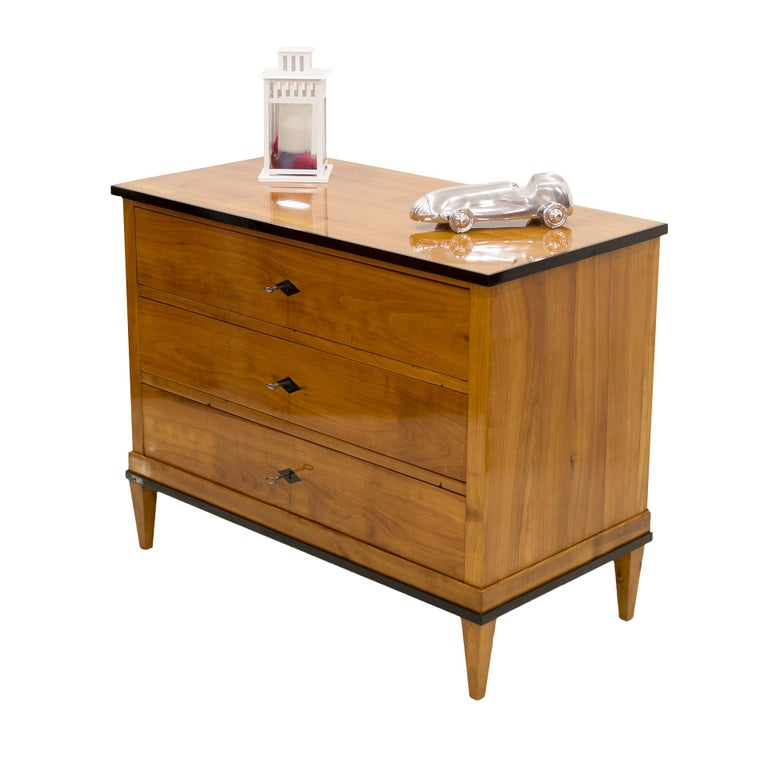 This three-drawer chest of drawers from the Biedermeier period dates back to the 19th century in Germany. The piece is in excellent condition and has been carefully renovated. It is made of cherrywood. The surface has been finished with polish which
