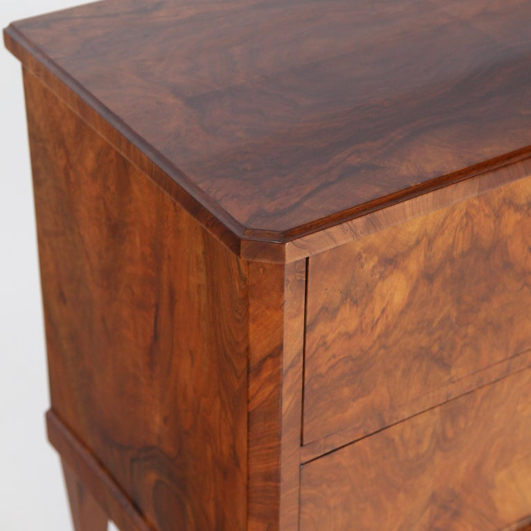 Two-drawered chest of drawers standing on pentagonal pointed feet with bevelled corners and very beautiful flamed walnut veneer. The keyholes with original leather fittings. Very nice restored and hand polished condition.