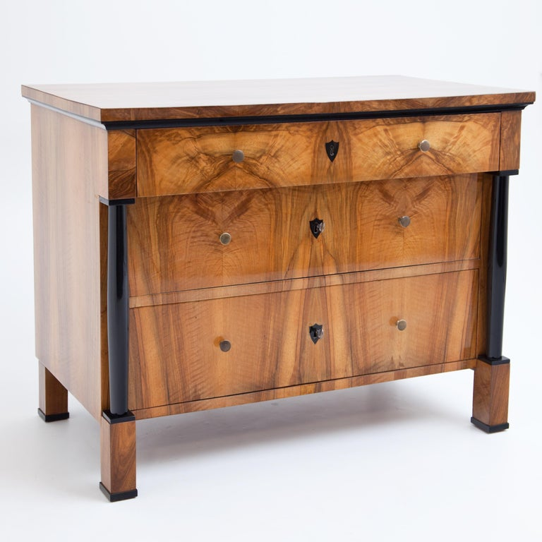 Three-drawer Franconian Biedermeier chest of drawers on plinthed square feet with ebonized full columns supporting the uppermost protruding drawer. Very beautiful walnut veneer. The chest of drawers with ebonised profile strip under the top and