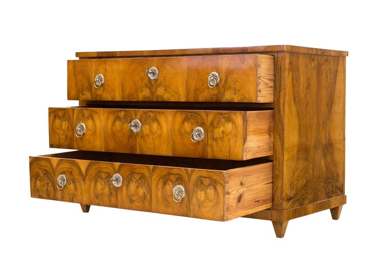 This is an original three-drawer chest of drawers from the Biedermeier period. It was made, circa 1830-1835 in Germany. The piece is made of coniferous wood, veneered with walnut wood. Finished with shellac varnish, hand-applied high-gloss tampon
