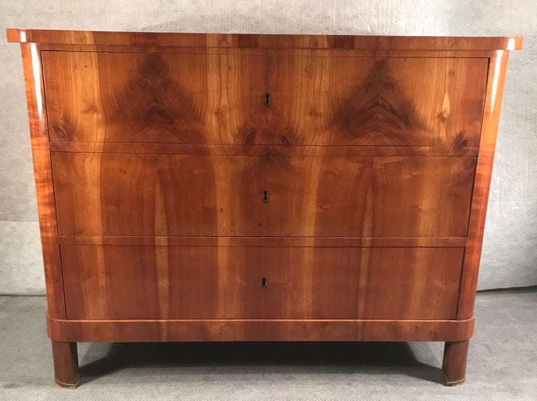 Biedermeier chest of drawers, South German, 1820. The three drawer commode stands out for its Classic, plain design and the beautiful cherry veneer decoration. It comes professionally refinished and French polished.
