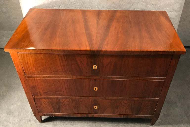 Original Biedermeier Commode, South German 1820. The commode or chest of drawers has a beautiful walnut veneer and inlaid bone escutcheons. It is in good condition. 