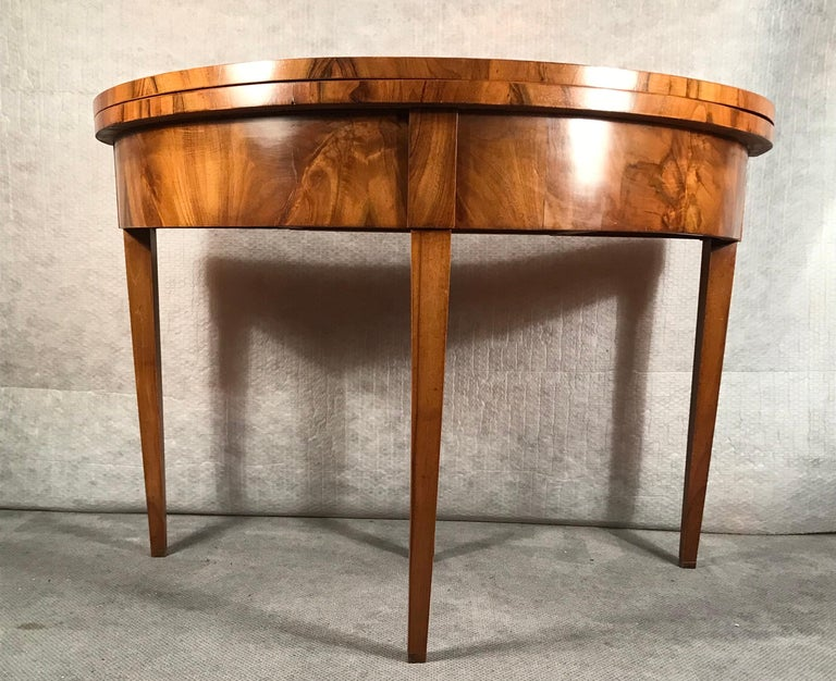 Biedermeier demilune table, South German, 1820. This beautiful table is decorated with a vivid walnut veneer. It is in very good condition and has a nice patina.