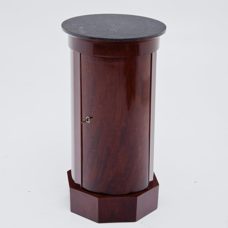 Biedermeier drum cabinet on octagonal base with round body and black marble top. Inside two shelves. Mahogany veneer.