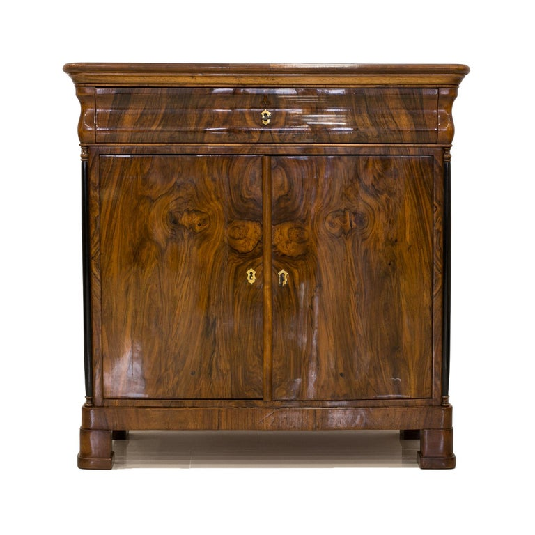 This Biedermeier-era commode was made in Germany in the first half of the 19th century. The furniture is made of coniferous wood, veneered with walnut veneer that presents beautiful wood patterns. It features one practical drawer in the top section