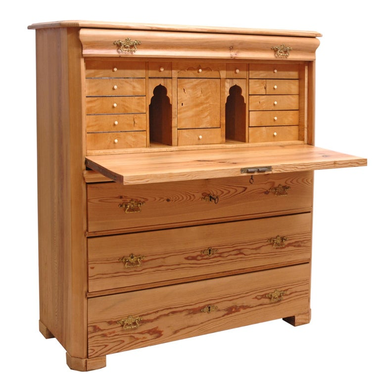 A handsome pine chest with fall front secretary offering a series of smaller drawers with pulls whose fascia is in flame birch. A small central cabinet is flanked by two open cubbies. Fall front is the perfect size for lap top. Doubles as a chest of