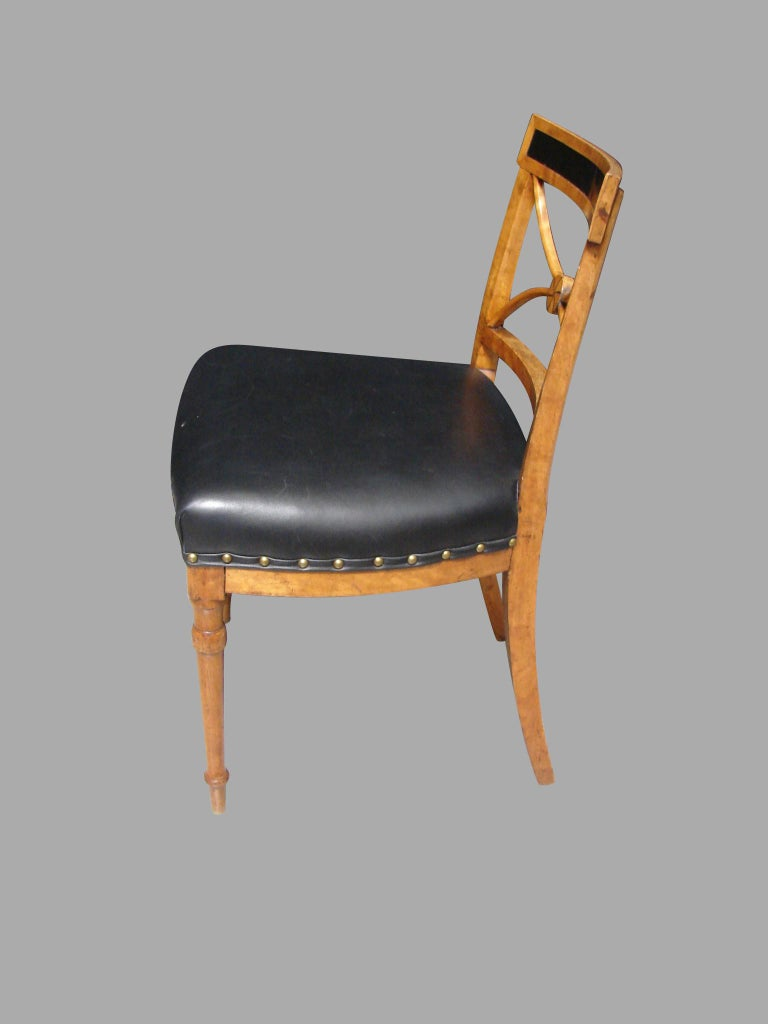A pretty Biedermeier satin birch side chair, the back with an ebonized top rail above a stylized splat centered with a boss, the seat upholstered in black leather, all supported on turned legs, circa 1820.